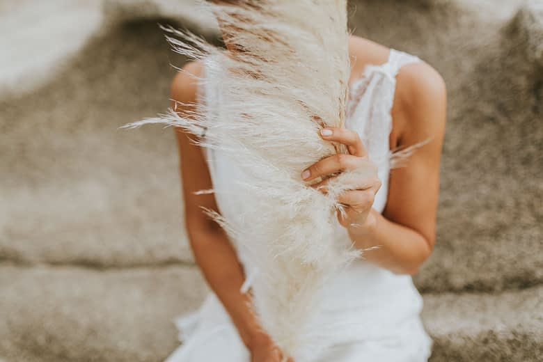 Hochzeit in Spanien - Die Braut verdeckt ihr Gesicht mit einem Pampagras und der Wind streicht sanft durch ihr Gesicht.
